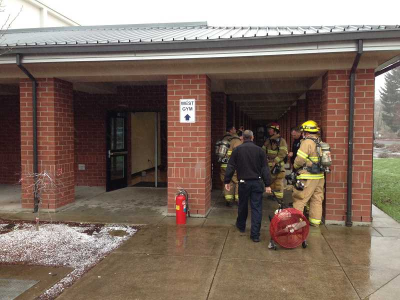 by: LAKE OSWEGO FIRE DEPARTMENT - Lake Oswego firefighters respond to a fire in a gym bathroom at Lake Oswego High School on Monday.