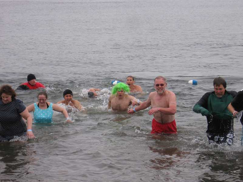 by: COURTESY OF TRESKE PRECISION MACHINING - Employees of Treske Precision Machining of Sherwood emerge from the Columbia River during last year's Polar Plunge. The business plans on participating once again, hoping to raise $4,500 in pledges.