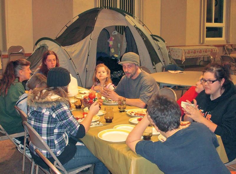 by: SUBMITTED - Reiko, at the head of the table, her husband, Tom, right, in hat, their children and some guests eat dinner together at St. Stephen Lutheran Church, when they were in the shelter there.