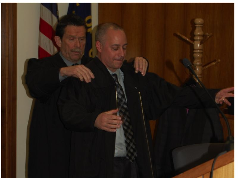 by: RAYMOND RENDLEMAN - Clackamas County Circuit Court Judge Michael C. Wetzel receives a black robe on Friday from Judge Robert D. Herndon.