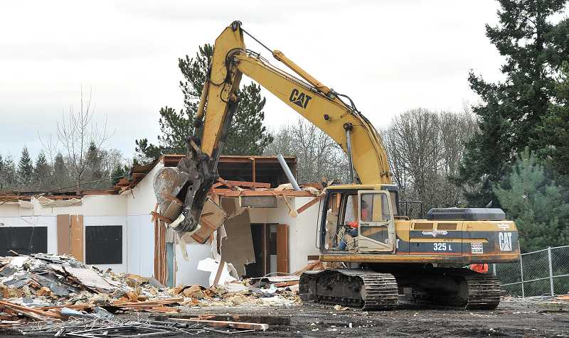 by: THE REVIEW, TIDINGS: VERN UYETAKE - A tractor works on Jan. 8 to tear down the building of the old Kasch's Nursery in West Linn. Chase Bank plans to construct a new branch in its place.