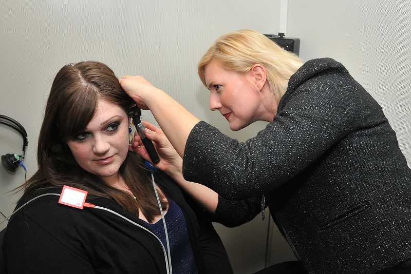 by: REVIEW, TIDINGS PHOTO: VERN UYETAKE - Hearing Rehab Center audiologist Jennifer Briggs examines a patient.
