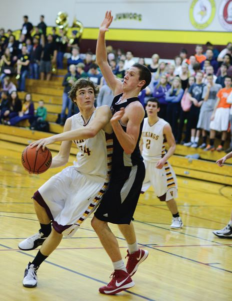 by: CHASE ALLGOOD - Forest Grove post Rodney Jensen (14) moves to the basket past a Tualatin defender in last Tuesday's 60-91 loss to the Timberwolves