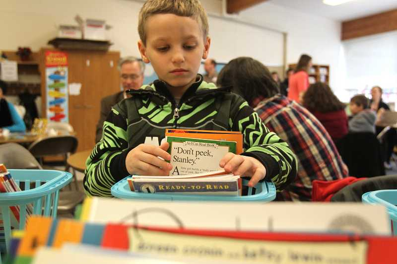by: TIMES PHOTO: JONATHAN HOUSE - Alex Georgeras looks through a stack of paperback books, one of which he's allowed to take home. Alex is part of the SMART reading program at McKinley Elementary School, where he receives extra attention to improve reading comprehension.
