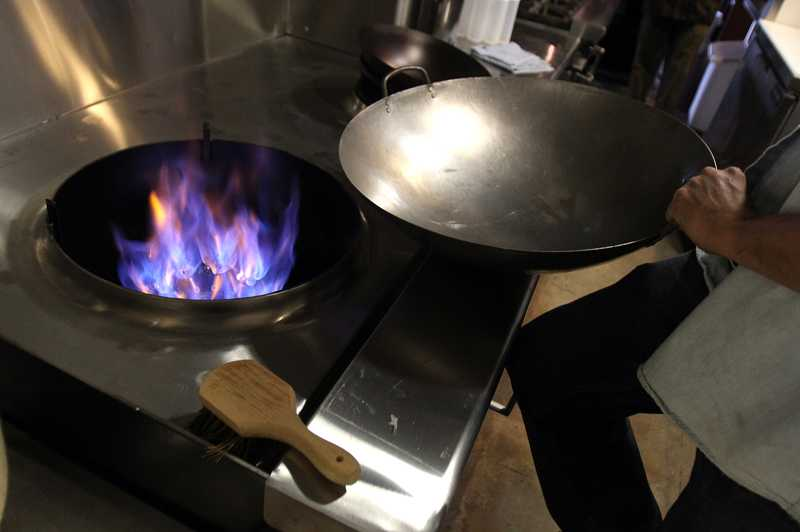 by: TIMES PHOTO: JONATHAN HOUSE - Ody Ratanaphupha shows off a specialty wok grill that he installed for his new restaurant, Planet Thai, at The Round in Beaverton.