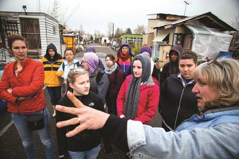 by: CHRISTOPHER ONSTOTT - Lisa Larson, who calls herself the 'advice chief executive officer' of Dignity Village, gives a group of University of Portland students a tour of the Northeast Portland homeless camp for their urban poverty immersion experience.