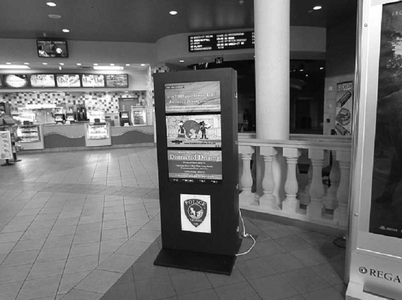 "by: SUBMITTED PHOTO. - The Tigard Police Department installed ""digital signage"" in the lobby of Bridgeport Regal Cinemas. This kiosk provides news and weather updates and public education materials, and was funded by a State Farm Insurance grant."