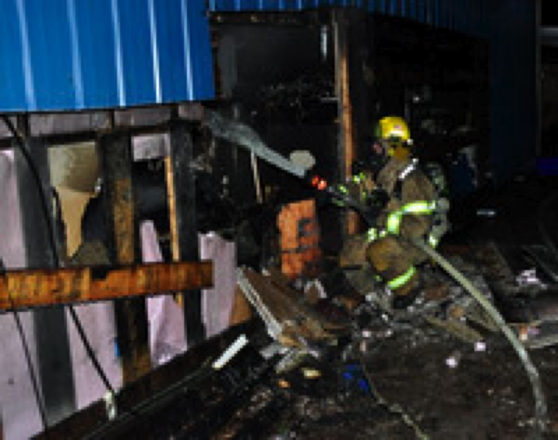 by: HILLSBORO FIRE AND RESCUE - Firefighters douse hot spots at a shop fire just outside Hillsboro early Thursday.