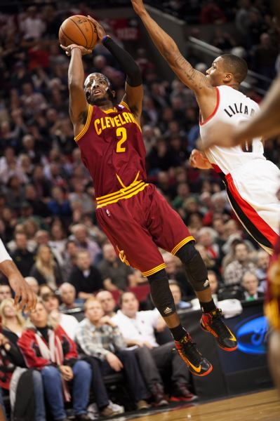 by: TRIBUNE PHOTO: MEG WILLIAMS - Cleveland's Kyrie Irving twists for a jump shot over Portland's Damian Lillard in the battle of point guards Wednesday night at the Rose Garden.