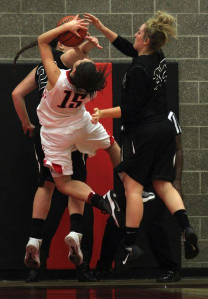 by: JONATHAN HOUSE - Clackamas junior wing Sydney Azorr (15) is hammered by Oregon City defenders Johanna Paine (right) and Catelyn Preston as she attempts to score a lay-up in Fridays game at Clackamas.