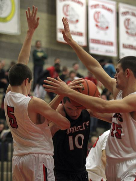 by: JONATHAN HOUSE - Clackamas defenders Brett Udland (5) and Taylor Stinson double up on Oregon City senior wing Nolan Muckenthaler (10) in last Fridays 68-60 win over the Pioneers.