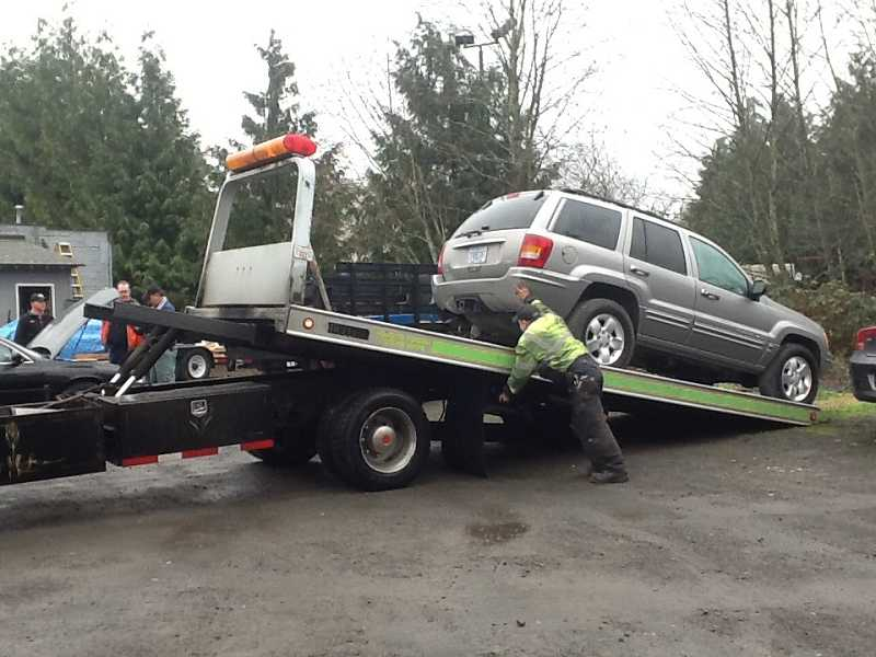 by: PHOTO COURTESY OF TIGARD POLICE - Police seize recovered stolen vehicle at Affordable Automotive.