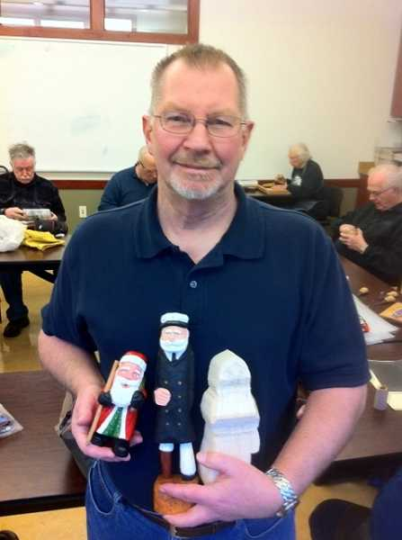by: SUBMITTED -  Loren Krebs displays examples of his carved Santa, Old Salt and Santa-in-progress.