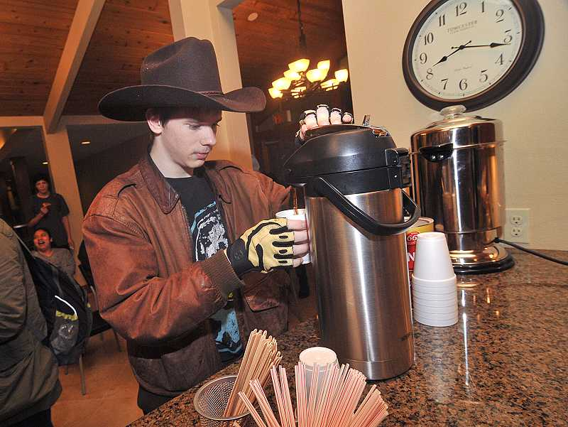 by: VERN UYETAKE -  West Linn High School senior Evan McNocol pours himself a cup of coffee before school starts at Coffee Cart, located in New Life Church.