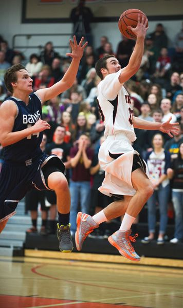 by: JEREMY DUECK - Scappoose's Paul Revis soars to the hoop with a Banks player in hot pursuit during last week's game.