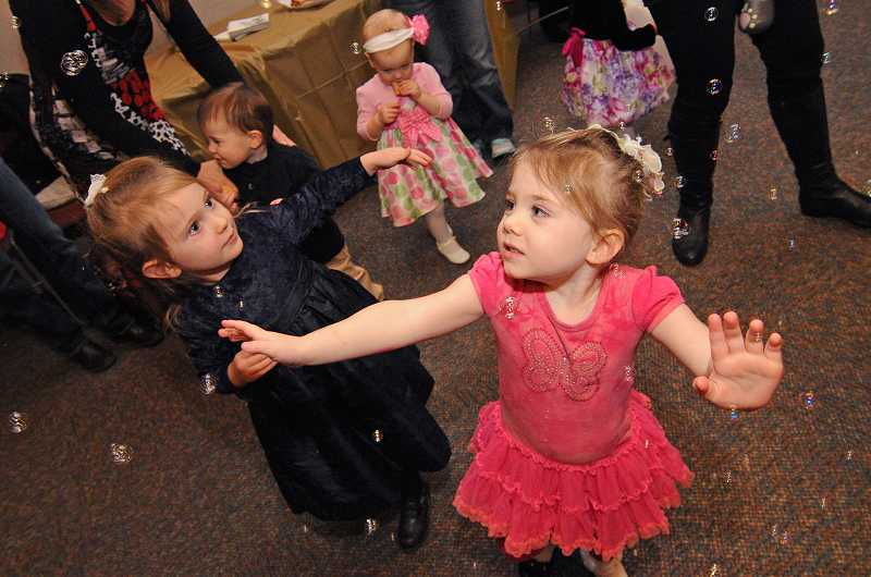 by: VERN UYETAKE - Grace Allori, 3, right, and Savanah Kling, 3, try to catch bubbles while dancing at the library's Snowflake Ball on Friday.