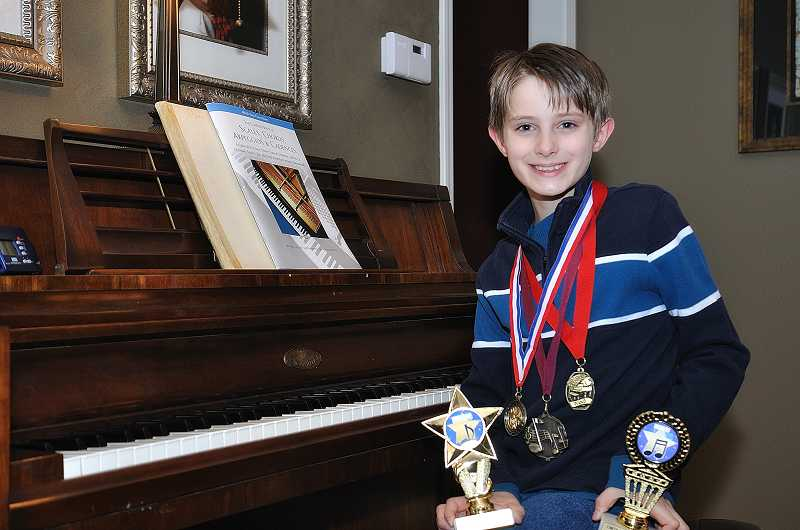 by: SUBMITTED - Sunset Primary School fifth-grader Haydn Maust poses with the piano awards he has received from the Oregon Music Teachers Association competitions.