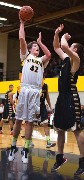by: JEREMY DUECK - St. Helens' Nathan Hunter goes up for a bucket during last week's game with Milwaukie.