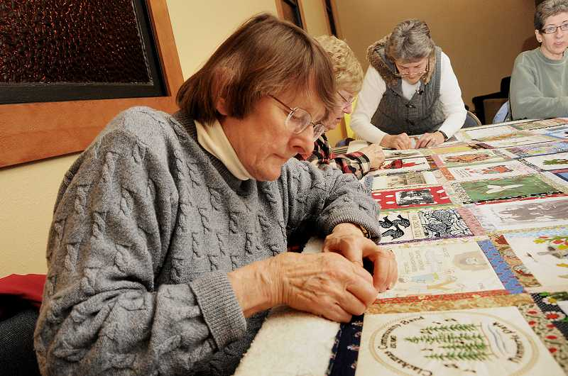 by: VERN UYETAKE - Roberta Staff concentrates on the putting together the quilt.