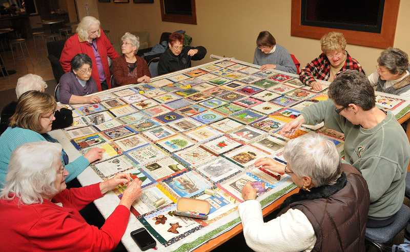 by: VERN UYETAKE - Quilters gathered last Jan. 17 at New Life Church to put together the pieces of the centennial quilt.