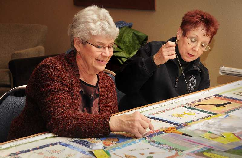 by: VERN UYETAKE - Alma Coston, left, and Lidia Salinas work on the quilt.