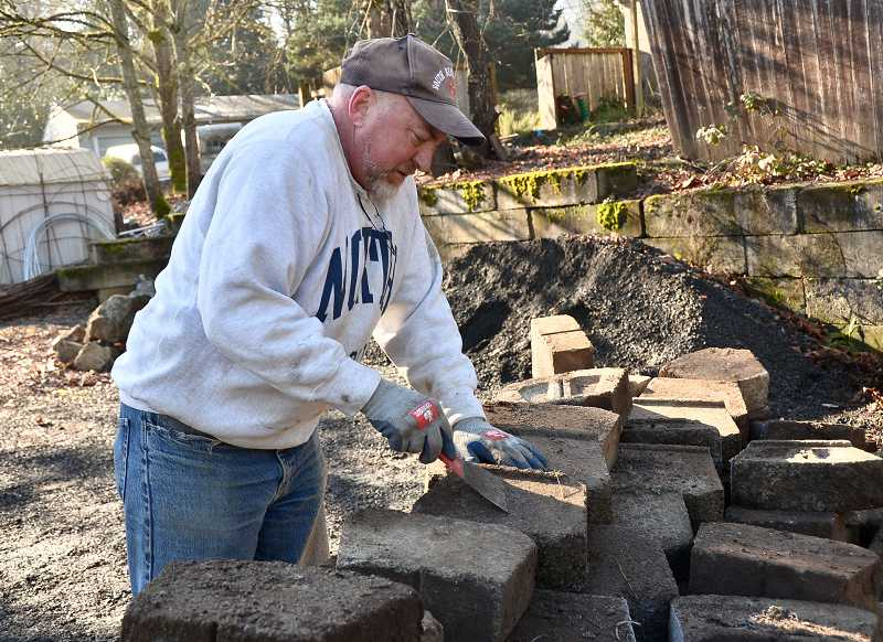 by: VERN UYETAKE - Ken Clifton cleans off recycled cement blocks to be used for a retaining wall along the Robinwood Stations driveway.