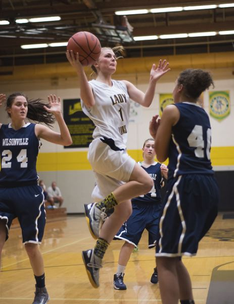 by: JEREMY DUECK - 'St. Helens' Nicole Harcourt drives to the basket during last Friday's game with Wilsonville. They Lady Lions lost their focus along the way, and lost the contest.