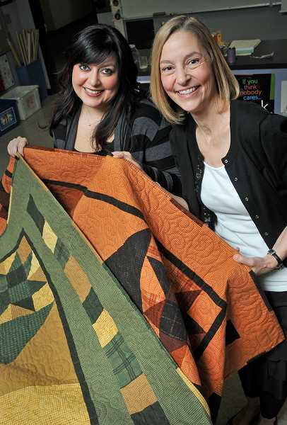 by: VERN UYETAKE  -  Janelle Minson, left, the co-chair of the substance-free West Linn High School grad party and quilter Jaylin Redden-Hefty display the quilts produced with the help of students.