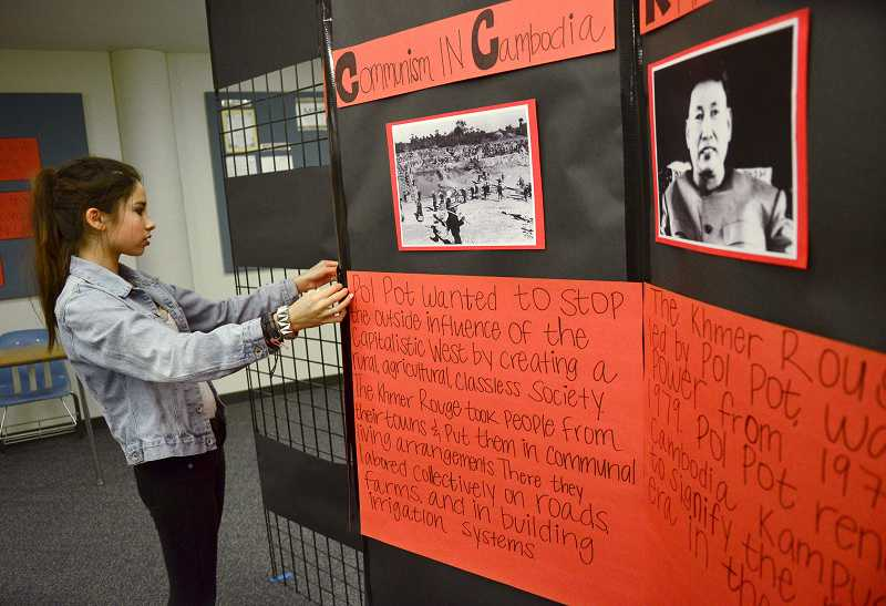 Lia Newman adjusts a display describing the Cambodian genocide.