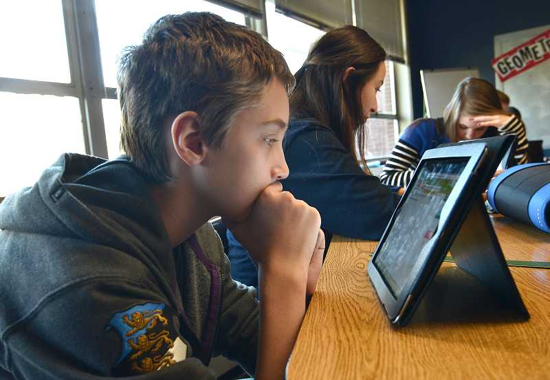 by: REVIEW PHOTOS: VERN UYETAKE - Robert Richard works on a math problem on an iPad.