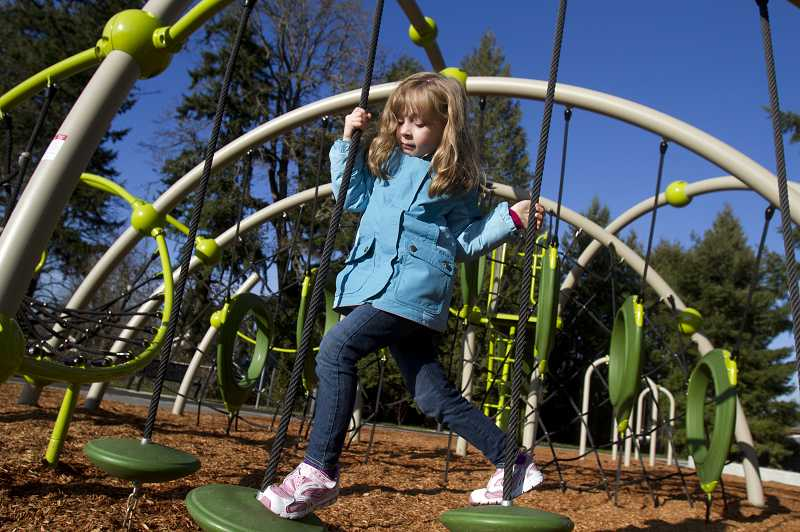 by: TIMES PHOTO: JONATHAN HOUSE  - Mackenzie Wood enjoys the new play structure at Evelyn M. Schiffler Memorial Park, which opened to the public on Friday.