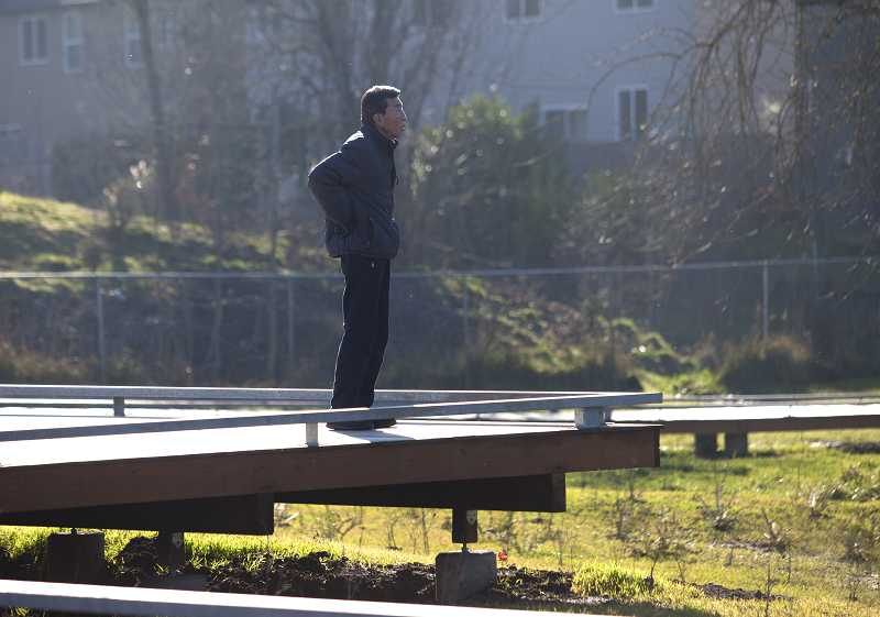 by: TIMES PHOTO: JONATHAN HOUSE - Hak Kim checks out a wetland area along the boardwalk in Evelyn Schiffler Memorial Park.