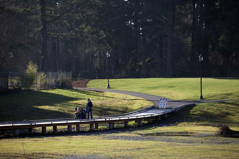 by: TIMES PHOTO: JONATHAN HOUSE - A family strolls across the new boardwalk that crosses a restored wetlands area in Evelyn M. Schiffler Memorial Park.