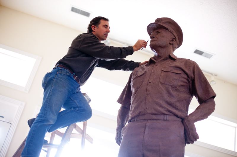 by: TRIBUNE PHOTOS: CHRISTOPHER ONSTOTT - Sculptor Rip Caswell works on the clay aspect of the larger-than-life Admiral Nimitz statue, which will be placed in Pearl Harbor this summer. Caswell uses photos to fine-tune details of the Nimitz sculpture.