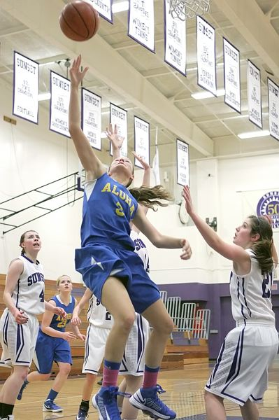by: MILES VANCE - SHE SCORES - Aloha senior Katie Newton lofts a shot over the Sunset defense during her team's 60-52 Metro League victory at Sunset High School on Jan. 17.