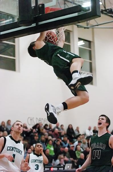 by: DAN BROOD - DUNK YOU VERY MUCH -- Tigard junior Bryan Berg goes up high for a slam dunk after coming up with a steal in the third quarter of Friday's game. Berg scored a game-high 23 points in the win.