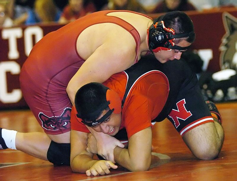 by: DAN BROOD - POWERFUL -- Tualatin High School senior Kenny Walther (left) has a firm grip on North Salem's Jose Macias in their 220-pound match. Walther won by pin in a time of 42 seconds.