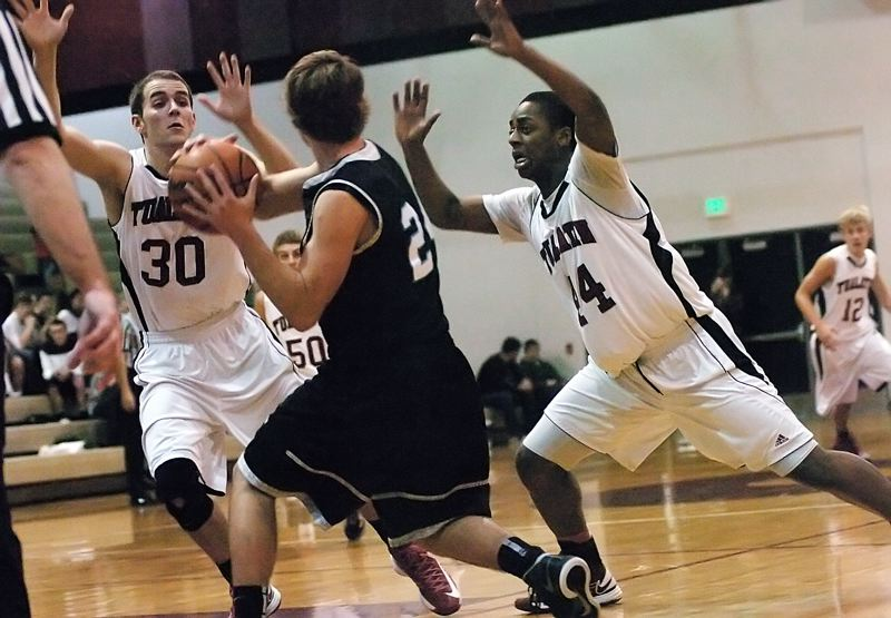by: DAN BROOD - TRAPPED -- Tualatin High School seniors C.J. Michael (30) and Junior Okon keep the pressure on Century senior Brad Bennett during the fourth quarter of Tuesday's game. The Timberwolves rallied to score a 104-98 victory.
