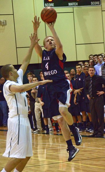 by: VERN UYETAKE - Lake Oswego's Cory Coombe attempts a buzzer beater in the Lakers' win over West Linn on Friday.