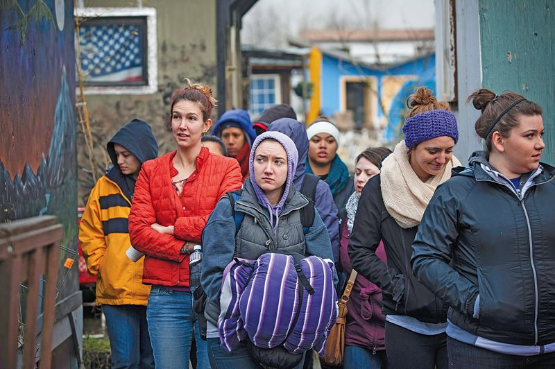 by: TRIBUNE PHOTO: CHRISTOPHER ONSTOTT - Hanna Hofford holds on tight to her sleeping bag as she, and other University of Portland students, get a tour of the Northeast Portland homeless camp Dignity Village.