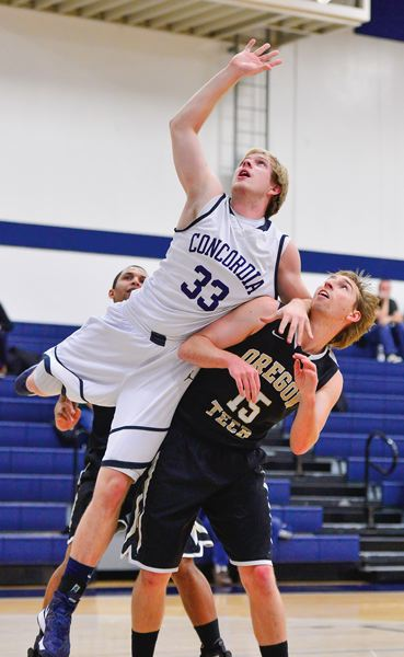by: PHOTO BY CHRIS OERTELL - Concordia sophomore and former Glencoe star Kory Kirwan (33) goes up for a rebound over David Clarke of Oregon Tech during a men's basketball game on Dec. 22.