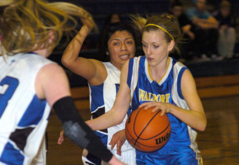 by: PAMPLIN MEDIA GROUP: DAVID BALL - Portland Waldorfs Anya Conlon drives to the basket between the double team efforts of Portland Lutherans Ayde Alvarado and Kaitlin Howard.