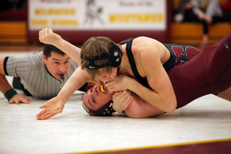 by: PAMPLIN MEDIA GROUP: JONATHAN HOUSE - Sandys Mike Stiles works for a pin at 145 pounds against Mountain Wetzel of Milwaukie during the Pioneers 72-0 dual win Wednesday night.