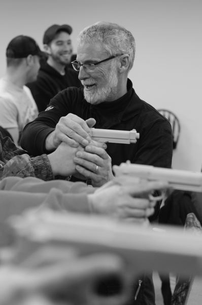 by: PHOTO BY: KATIE WILSON - Gregg Smith, gun safety instructor and range master at the Clatskanie Rifle and Pistol Club, shows students the proper way to hold and aim a gun using plastic replicas that replicate the weight and feel of real firearms.