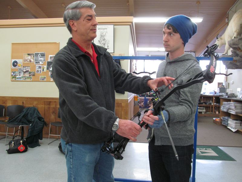by: PHOTO BY: ELLEN SPITALERI - Chuck Pedracini shows David Calhoun the advantages of using a compound bow.