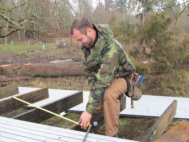 by: PHOTO BY ELLEN SPITALERI - David Izar, owner of Buildstrong Construction, measures the supports of the overlook, before attaching the surface of the deck.