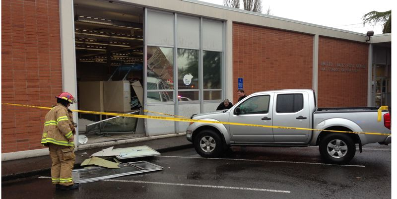 by: COURTESY OF LAKE OSWEGO FIRE DEPARTMENT - A firefighter checks the damage Wednesday morning after a small pickup driven by a man in his 50s slammed into a glass and metal panel at the Lake Oswego Post Office on Fourth Avenue. One mail carrier was slightly injured when a metal table fell on her.