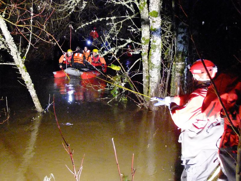 by: COURTESY OF PORTLAND FIRE & RESCUE - Portland firefighters and the swift water rescue team used a raft and ropes to pull a man and woman to safety Tuesday afternoon from an island in Johnson Creek.