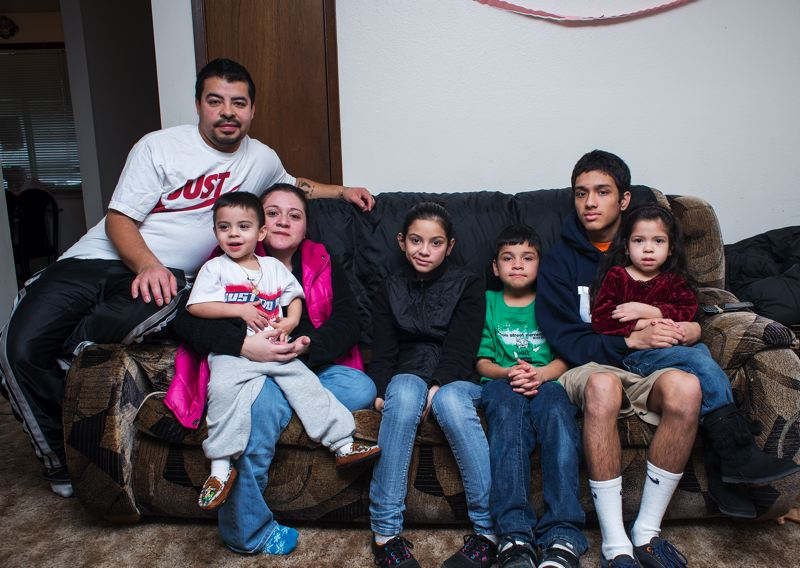 by: CHASE ALLGOOD - Elsa Barbosa (third left) sits in her current home with her husband and five children, where she hopes they can stay if her treatment is unsuccessful.