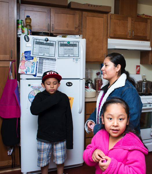 by: NEWS-TIMES PHOTO: CHASE ALLGOOD - Gertrudis Aragon (center) and her children, Rafael Santiago, 9, and Angelica Santiago, 5, gather in their Juniper Gardens kitchen for snacks and to show off their gas stove.
